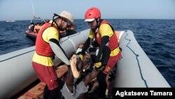 Les membres de l'ONG humanitaire espagnole Proactiva Open Arms, portent le cadavre d'un migrant après une opération de sauvetage au large des côtes libyennes le 4 octobre 2016.