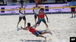 In this picture made available by the Tasnim News Agency, an unidentified Iranian volleyball player defends a ball against his Turkish competitors during the International Beach Volleyball Championships at Iran's Kish Island, Feb. 15, 2016.