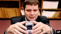 Chris Danielsen, juru bicara Federasi Nasional Tunanetra, memotret dokumen dengan ponsel untuk memperlihatkan bagaimana teks di dokumen tersebut dapat diubah menjadi audio. (Foto: Dok)
