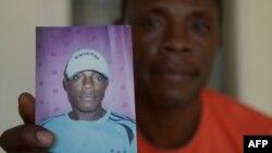 Beliby Ferdinand Bengondo memegang foto mendiang saudara laki-lakinya, penyerang Kamerun Salomon Bengondo. (AFP/Adek Berry)