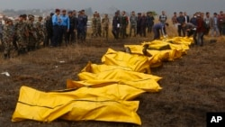 Nepalese rescuers attend to bodies of victims after a passenger plane from Bangladesh crashed at the airport in Kathmandu, Nepal, March 12, 2018.