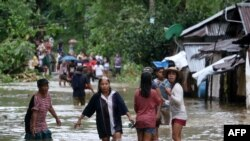 Warga di tengah banjir di Brgy Calingatngan, di Borongan, Samar timur, Filipina tengah, 16 Desember 2017.