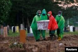 Para petugas membawa peti jenazah seorang dokter yang meninggal karena Covid-19, selama pemakaman di Jakarta.