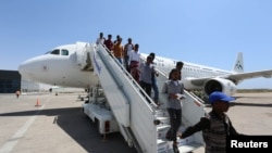 Daallo Airlines staff usher in passengers from Jeddah after their airline, Daallo Airlines operated by Air Mediterranee, arrived at the Aden Abdule International Airport in Somalia's capital Mogadishu, February 17, 2015.