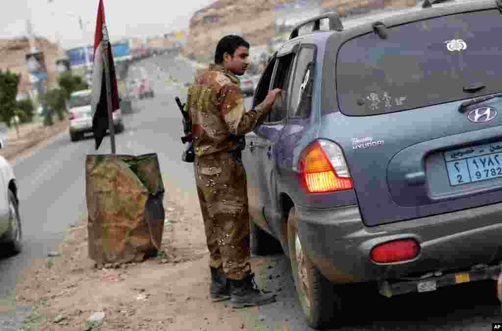 A Yemeni soldier inspects cars on a street leading to the U.S. embassy in Sanaa, August 4, 2013.