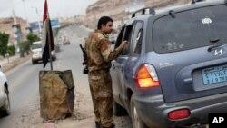 一位也门士兵在一处通往美国驻也门萨那领事馆的检查站正检查一辆汽车。