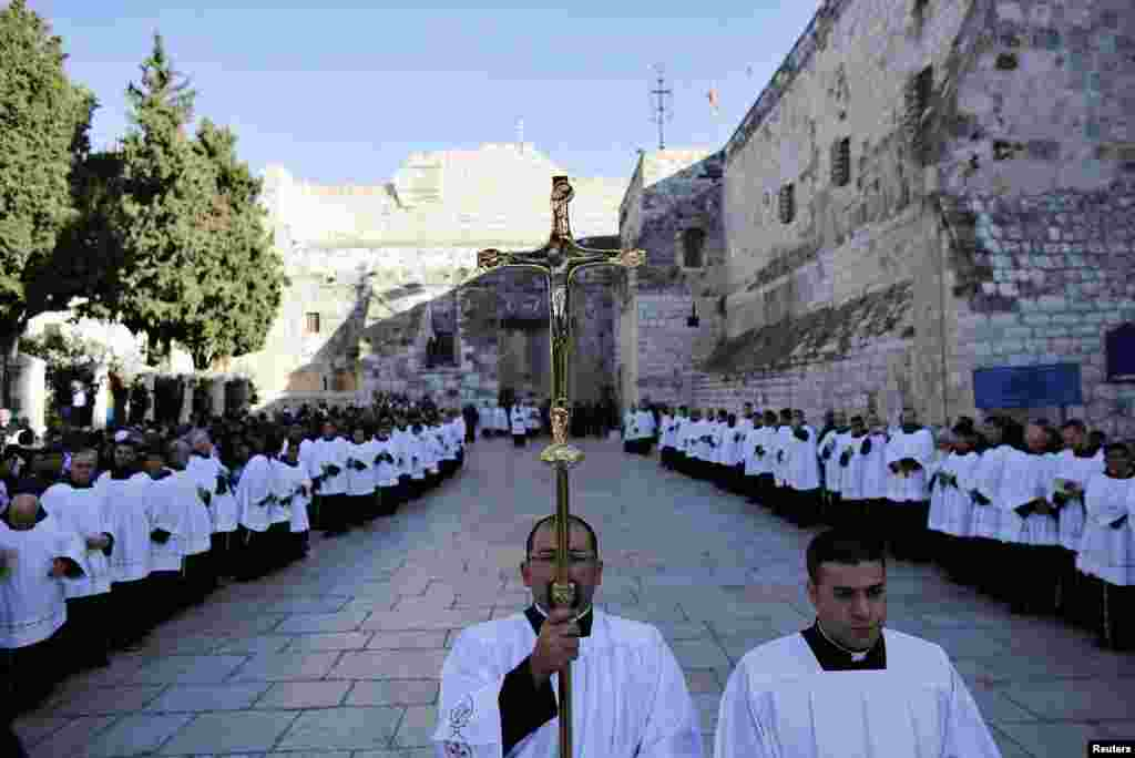 A member of the clergy holds a cross as he waits for the arrival of the Latin Patriarch of Jerusalem Fouad Twal outside the Church of the Nativity, the site revered as the birthplace of Jesus, in the West Bank city of Bethlehem, December 24, 2012.