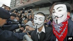 Pro-democracy demonstrators wearing Anonymous masks, scuffle with police during a protest against the Chinese government's meddling into the Hong Kong's chief executive election, in Hong Kong, April 1, 2012.