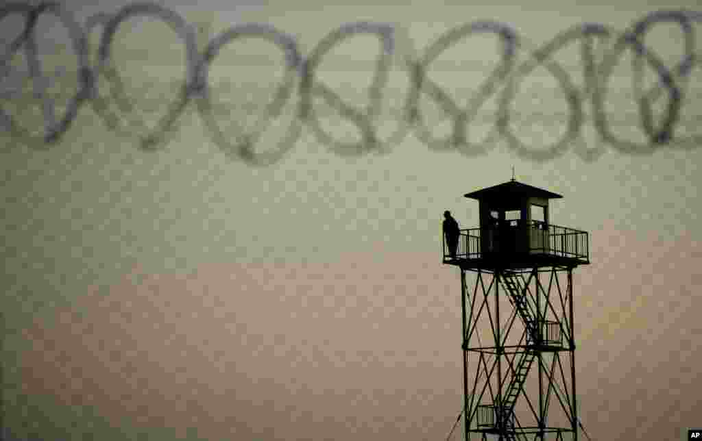 A man watches from a border tower in Serbia near the Hungarian village Roszke, southern Hungary, Sept. 12, 2015. Hundreds of thousands of Syrian refugees and others are still making their way slowly across Europe, seeking shelter where they can, taking a bus or a train where one is available, walking where it isn't.