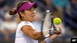 Li Na, de China, regresa la bola a Aleksandra Wozniak, de Canadá.