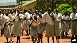 FILE - In this photo taken July 30, 2017, girls take a break at the Loreto Secondary School, the region's only all-girls boarding school where staff require each girl's guardian to sign a form promising not to remove the child from school until graduation, in the town of Rumbek, South Sudan.