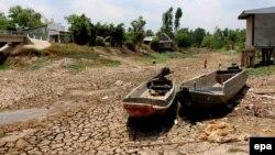 Hai chiếc tàu nằm trên mặt đất nứt nẻ vì hạn hán tại tỉnh Cà Mau, Việt Nam, ngày 18/4/2016.