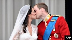 U skladu sa tradicijom, britanski princ Vilijam poljubio je svoju ženu, Kejt, vojvotkinju od Kembridža, na balkonu Bakingemske palate posle ceremonije venčanja.
