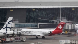 Baggage carts make their way past a Helvetic Airways aircraft from which about $50 million worth of diamonds were stolen on the tarmac of Brussels international airport February 19, 2013. (AP Photo/Yves Logghe)