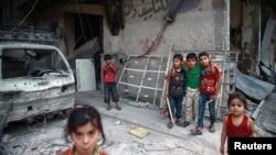 Trẻ em tụ tập gần những tòa nhà bị hư hại ở Đông Ghouta, Damascus, Syria, ngày 17 tháng 7, 2017.