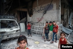 Children are seen near rubble of damaged buildings in the Damascus suburb of Eaterm Ghouta, Syria, July 17, 2017.