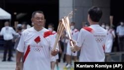 Le président du Comité olympique japonais, Yasuhiro Yamashita, à gauche, effectue un baiser de la torche lors de l'événement final du relais de la torche pour les Jeux olympiques de Tokyo au complexe du gouvernement métropolitain de Tokyo, vendredi 23 juillet 2021.