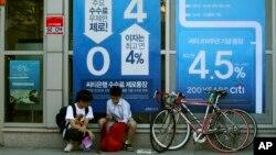 Học sinh trung học Hàn Quốc ngồi trước áp phích quảng cáo lãi suất của ngân hàng tại Seoul.