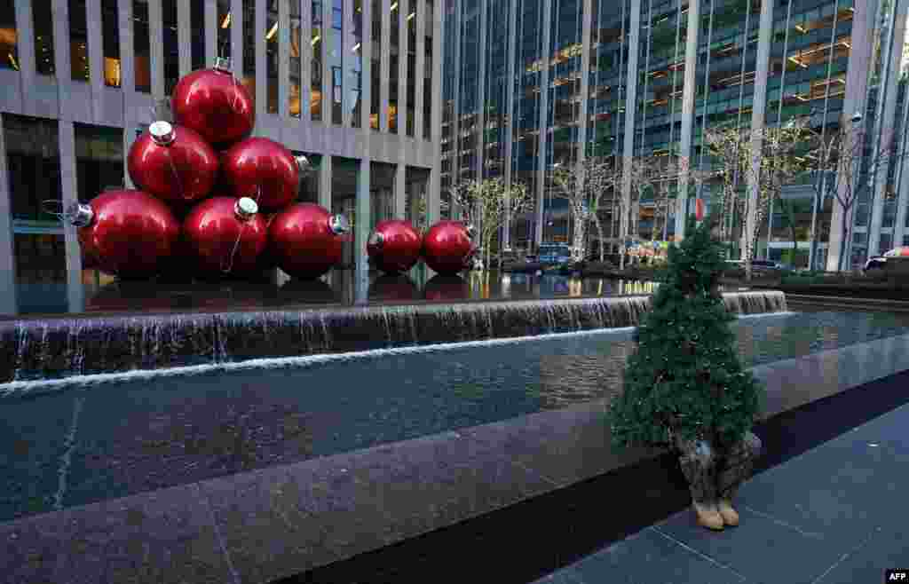 "Street performer Thomas Liberto from Bel Air, Maryland, who goes by the social media name ""Mr. Christmas Tree,"" sits by Christmas decorations around midtown New York, Dec. 19, 2019."
