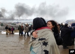 A couple embraces as opponents of the Dakota Access pipeline leave their main protest camp, Feb. 22, 2017, near Cannon Ball, N.D., as authorities were preparing to shut down the camp in advance of spring flooding season. The Army Corps of Engineers ordered the camp closed at 2 p.m. Wednesday.