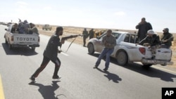星期天一名反政府戰鬥人員手持步槍衝向一輛汽車