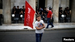 A refugee child holds a flag during a protest, called by the 'United against Rascism and the Fascist Threat' movement, demanding better conditions for refugees in the Greek camps, in front of the City Hal in Athens, June 9, 2016.