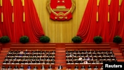 China's President Xi Jinping and other delegates listen as China's Premier Li Keqiang (not pictured) delivers a government work report during the opening session of the National People's Congress (NPC) at the Great Hall of the People in Beijing, China, Ma