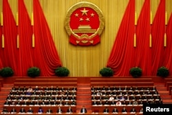 China's President Xi Jinping and other delegates listen as China's Premier Li Keqiang (not pictured) delivers a government work report during the opening session of the National People's Congress (NPC) at the Great Hall of the People in Beijing, China.