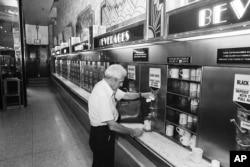 Seorang pelanggan membeli secangkir kopi di satu-satunya restoran Horn & Hardart Automat yang masih bertahan di tengah kota Manhattan, New York City, 8 Juni 1987. (AP)