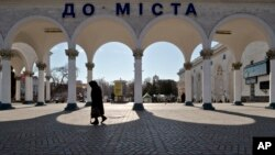 An elderly woman walks at the main railway station in Simferopol, Ukraine, Friday, March 14, 2014