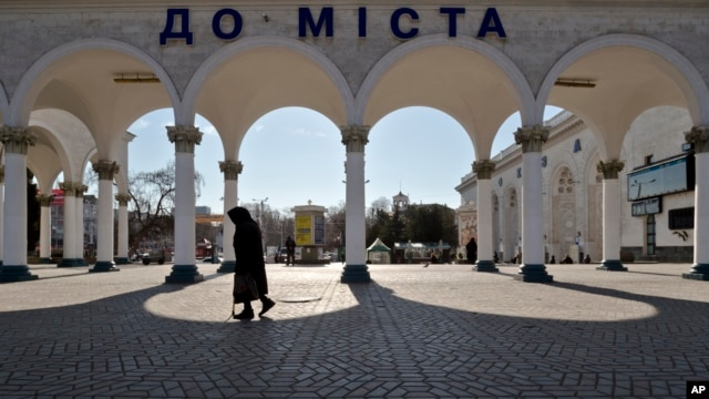 An elderly woman walks at the main railway station in Simferopol, Ukraine, Friday, March 14, 2014
