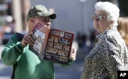 A vendor shows Marie Ross of Pennsylvania a magazine during her visit to Dealey Plaza in Dallas, Oct. 25, 2017.