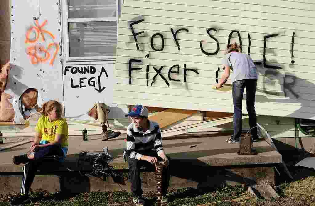 Lindsey Murray, de 15 años, pinta en lo que queda de la casa de su abuela en Harrisburg, Illinois, que está a la venta para quienes deseen un proyecto.