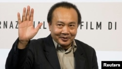 FILE - Cambodian director Rithy Panh waves as he poses during a photo call, Oct. 24, 2008.