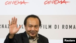 Cambodian director Rithy Panh waves as he poses during a photo call, Oct. 24, 2008 (File)