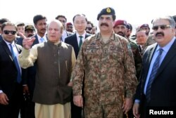 In this Nov. 13, 2016 photo, Pakistan's Prime Minister Nawaz Sharif and Army Chief of Staff General Raheel Sharif, right, attend the inauguration of a port in Gwadar, Pakistan.