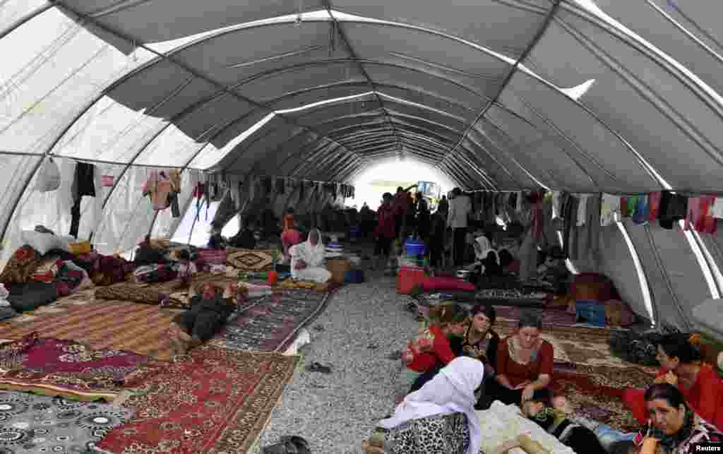 Displaced people from the minority Yazidi sect, fleeing violence in Iraq, take refuge in the southeastern Turkish town of Silopi, near the Turkish-Iraqi border crossing of Habur, Aug. 12, 2014.