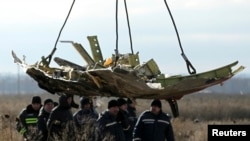 FILE - A crane transports a piece of the Malaysia Airlines Flight MH17 wreckage at the crash site in eastern Ukraine's Donetsk region, Nov. 20, 2014.