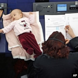Denmark's member of the European Parliament Hanne Dahl (R) takes part with her baby in a voting session at the European Parliament in Strasbourg March 26, 2009