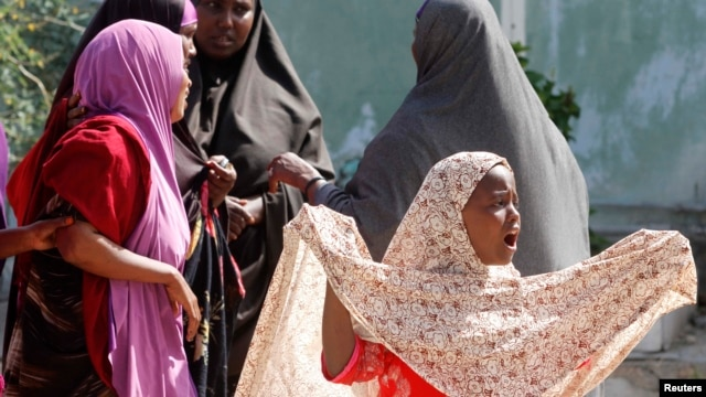 A Somali girl cries at the scene where her mother died as a result of a blast while sweeping a section of Taleh street in Mogadishu, August 3, 2014.