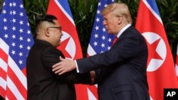 FILE - U. S. President Donald Trump shakes hands with North Korea leader Kim Jong Un at the Capella resort on Sentosa Island, June 12, 2018 in Singapore.