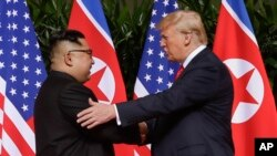 FILE - U.S. President Donald Trump shakes hands with North Korea leader Kim Jong Un at the Capella resort on Sentosa Island, June 12, 2018, in Singapore.
