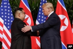 U. S. President Donald Trump shakes hands with North Korea leader Kim Jong Un at the Capella resort on Sentosa Island, June 12, 2018 in Singapore.