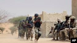Les forces spéciales nigérianes courent et passent devant des éléments de la troupe tchadienne lors d'une formation conjointe sur la libération des otages à Mao, Tchad, 7 mars 2015