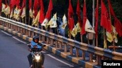 Seorang pria mengendarai sepeda motor melewati jembatan layang yang dihiasi bendera-bendera partai politik menjelang pemilu, Jakarta, 6 April 2019. (Foto: Reuters)