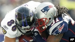 Baltimore Ravens tight end Todd Heap, left, takes a hit from New England Patriots safety Brandon Meriweather during an NFL football game at Gillette Stadium in Foxborough, Mass., 17 Oct 2010
