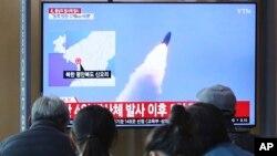 한국 서울역에서 시민들이 북한이 미사일로 추정되는 발사체를 발사했다는 보도를 시청하고 하고 있다.