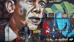 دوچرخه سوار دوچرخه خود را به دیوارنگاره عظیمی از اوباما در نایروبی، پایتخت کنیا تکیه می دهد. ۲۲ ژوئیه ۲۰۱۵