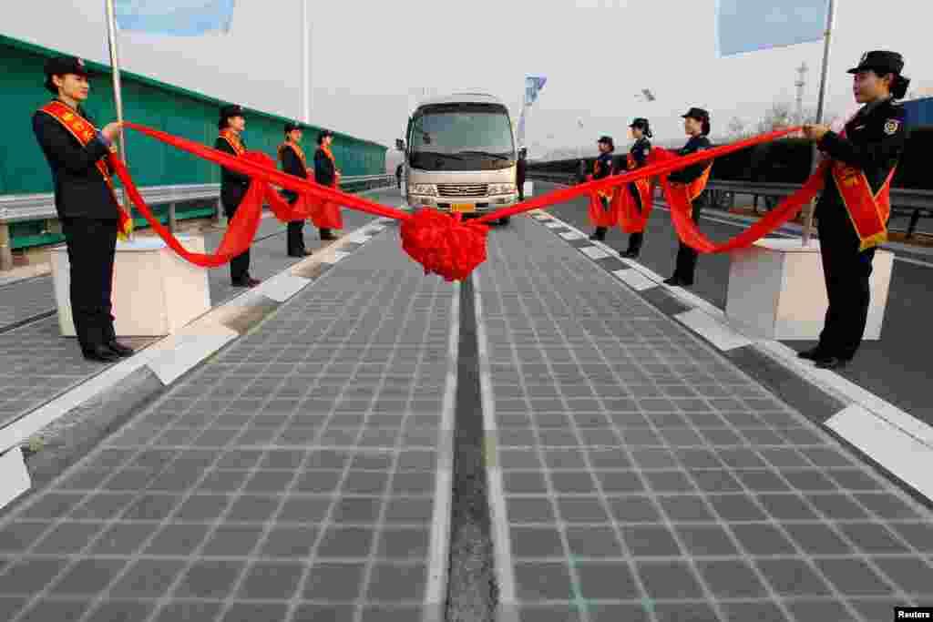 """山东济南的光伏高速公路亮相,巴士在公路上(2017年12月28日)。中国央视说,这是由中国""""完全自主知识产权研发与铺设的全球首段光伏高速公路"""",""""目前,半透明的路面已铺设完毕,一些车辆已经开始在路面上进行测试。 """""""