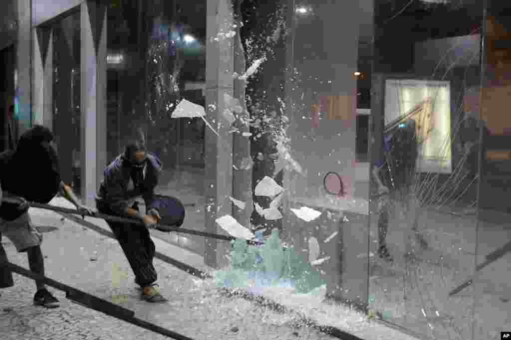 Protesters shatter the glass walls of a bank during a demonstration against proposed reforms by the federal government, in Rio de Janeiro, Brazil, March 15, 2017.